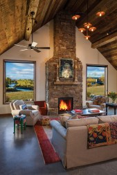 In the main living area a painting by Matt Flint hangs over the mantel and a vaulted ceiling lends an expansive air to the space. Low maintenance concrete floors span the entire house. The windows flanking the Harlowton stone fireplace look to the Shields River and the view that inspired the building site from architect Jonathan Foote's first visit.
