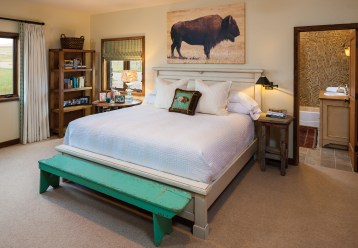 In the master bedroom a dramatic bison photograph by Nancy Etheridge printed on canvas makes a statement in a simple space. The colorful bench is from Round Top Antiques Fair in Texas.