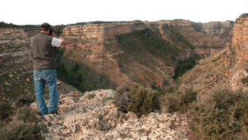 The author's friend, Bruce, scans the Middle Fork chasm with binoculars. The edge of the gorge offers extraordinary views of soaring raptors and the river murmuring far below.