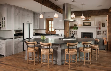 Contemporary, gray-painted cabinets and smooth, lightcolored paint offset reclaimed elements in the kitchen.
