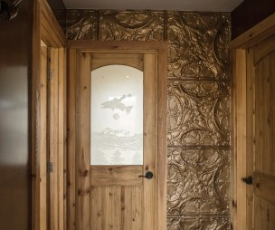 The inset glass in a bathroom door features an original etching by Reece.