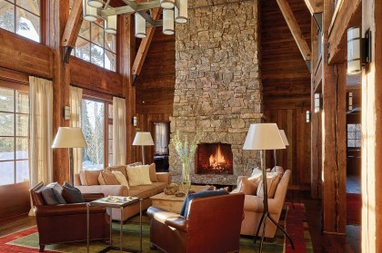 In the great room, the warm hue of the upholstery in the furnishings echoes the red-brown tones of the timbers, floor and walls. The elegant span of native stone in the fireplace creates a streamlined effect in the rustic palette.
