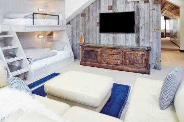 Guest quarters are tucked away upstairs, where a bunk room doubles as a family room.