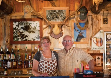 Buckhorn Bar proprietors, Tammy and Frank Dellwo, pose behind the bar. It's fun to test your knowledge of the local wildlife and try to name all the impressive mounts on the wall over a delicious burger here.
