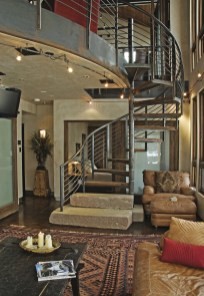 Jumping to an industrial Modern design, Larry Pearson's signature remains with natural elements, such as the cut stone at the base of the stairs, a natural color scheme and wood accents.