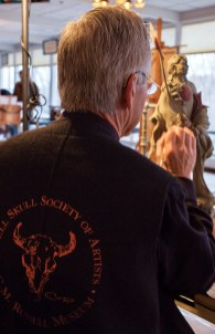 Sculptor Jerry McKellar, wearing a Russell Skull Society honorary vest, works on a piece during a Western Art Week quick finish event.