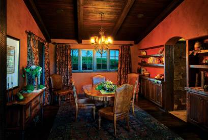 Plaster walls, wood ceiling, and cabinets constructed from planks from the family farm provide intimacy in the dining room.