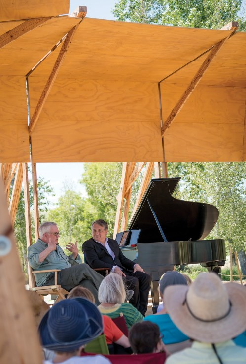 Artist Stephen Talasnik, far left, and music director Christopher O'Riley sit in conversation below the portable Tiara acoustical shell, designed by Alban Bassuet and Willem Boning.