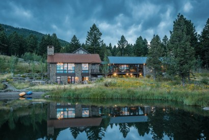 The rustic mountain home faces out toward a stocked pond, with views of Ennis Lake and the Madison Range in the distance.