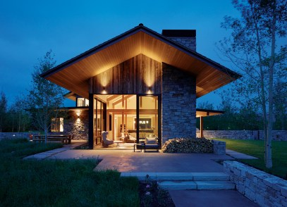 A gabled roof, reclaimed barnwood and natural stone create a rustic mountain exterior for this home near Jackson, Wyoming. The inside unlocks a world of Scandinavian simplicity with light, airy spaces and clean lines