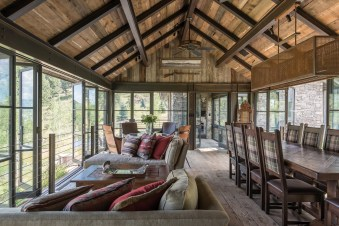 The glass- and steel-lined bridge that connects the two parts of the home is a favored interior hang-out spot, featuring a dining and sitting area, a game table, and a small office.