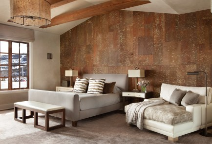 In the master bedroom, a bark wall covering adds depth and contrasts with the soft luxe bedding.