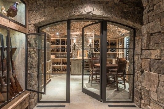 The homeowners' gun collection lines the entrance to the wine cellar.