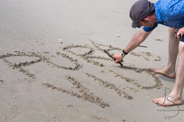Aaron writing Pura Vida in the sand