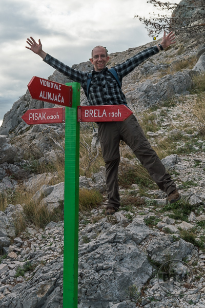 Aaron behind a direction sign in Croatian
