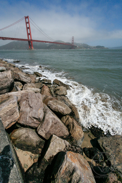 Rocks lining the San Francisco Bay in front of the Golden Gate Bridge | BIG tiny World Travel
