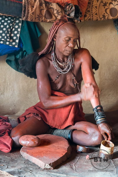 Elderly Himba woman making traditional makeup
