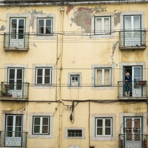 A man standing on his balcony outside a yellow building in Lisbon, Portugal
