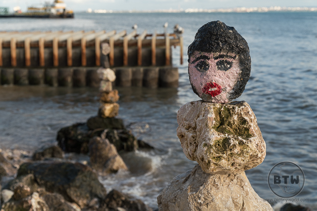 A cairn painted to look like a person on the Lisbon coastline in Portugal