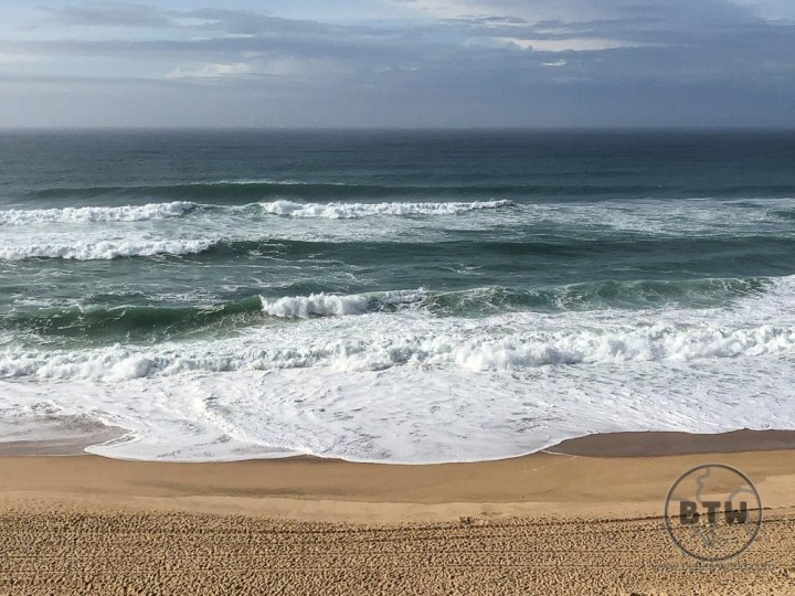 Waves crashing on a sandy beach at Santa Cruz, Portugal