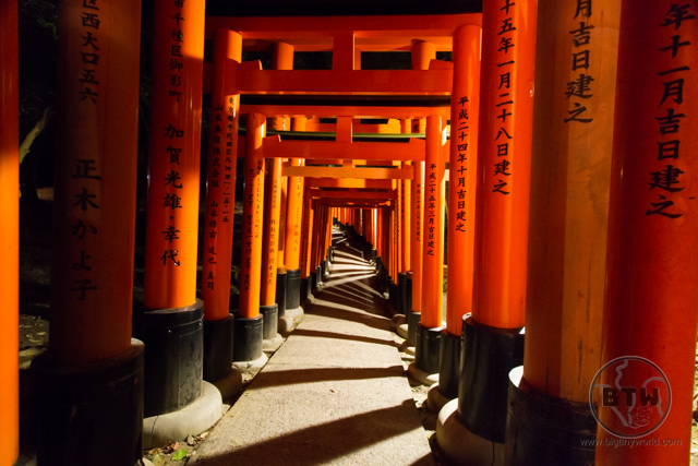 A tunnel of torii at night at the Fushimi Inari Shrine in Kyoto, Japan