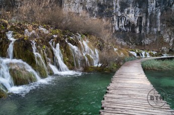 A boardwalk winding next to a series of waterfalls in Plitvice Lakes National Park in Croatia