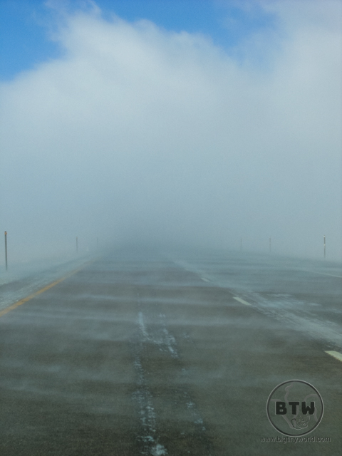 A low cloud obscuring the highway in Idaho as snow blows across the road