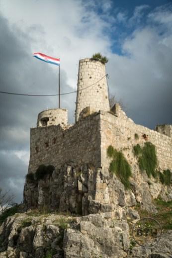 A tower and Croatian flag at Klis Fortress near Split, Croatia