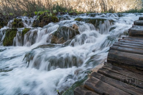 A boardwalk along a wide waterfall in Plitvice Lakes National Park, Croatia