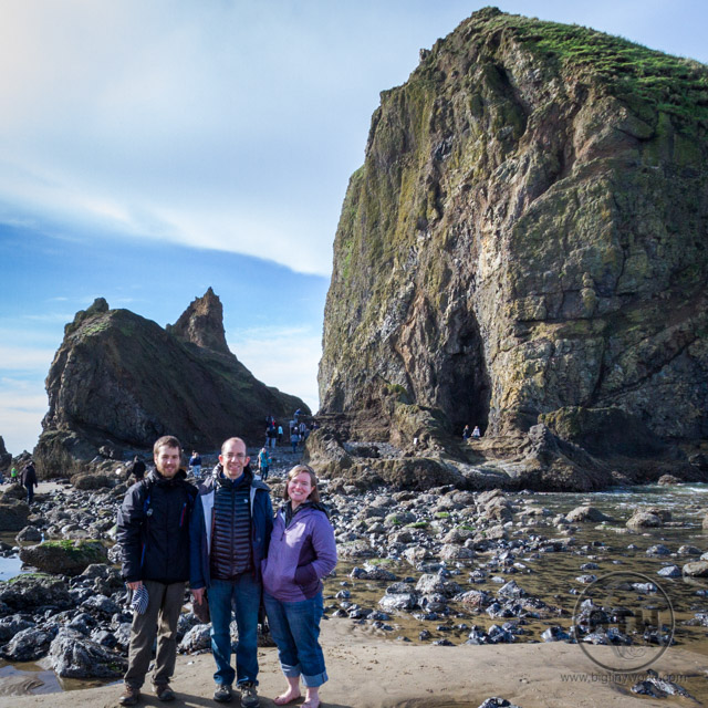 Aaron and Brianna posing with a couchsurfer, Leo, at Cannon Beach, Oregon