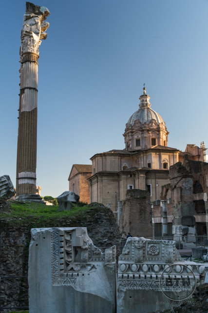 Ruins of the Roman Forum in front of a restored historic building in Rome, Italy