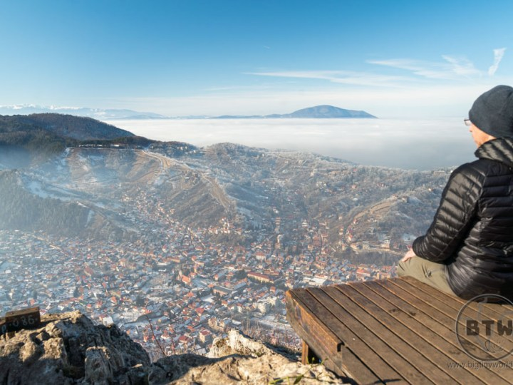 Aaron sitting at a viewpoint overlooking Brasov, Romania