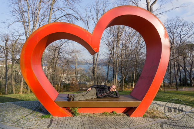 Aaron lounging on a bench under a heart in a park in Istanbul, Turkey