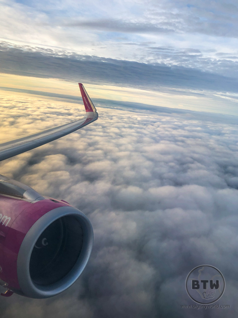 A plane wing high above the clouds