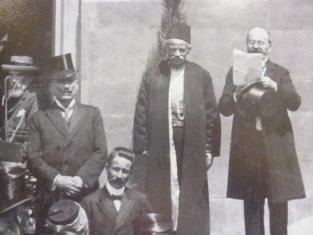 Муяга Комадина на трибуне (слева от читающего речь). Автор неизвестен, public domain