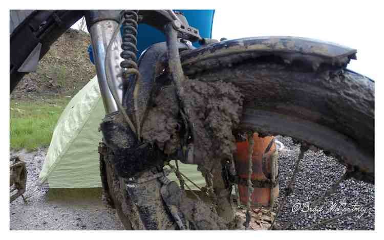 A discarded toilet brush on the side of the road was used to clean the mud off the bike