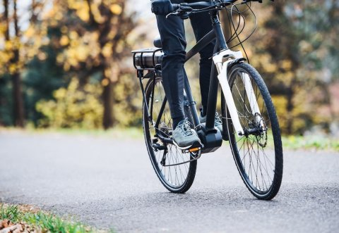 an-unrecognizable-man-on-electrobike-cycling-outdo-9P5CQFG-min