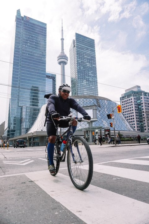smiling-professional-cyclist-riding-in-megapolis-min
