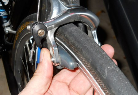 Squeeze the calipers until they almost touch the rim.