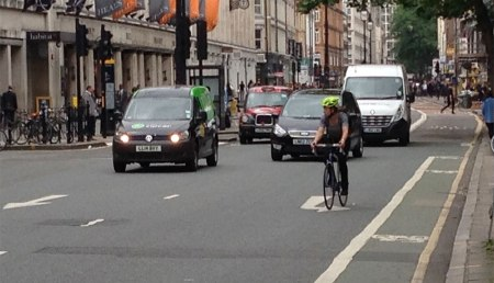 A cyclist takes the lane to beat cars to the next stoplight. Tottenham Court Rd.