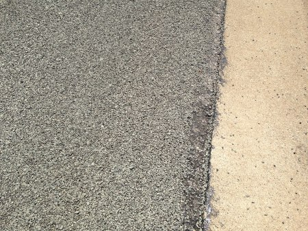 The dreaded chip sealed surface. Loose gravel will cover the road for some time to come.