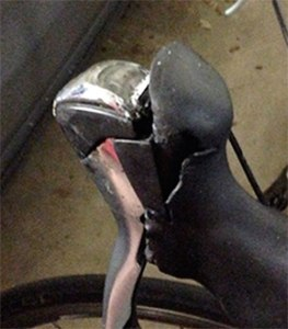 It's easy to see how the hood separates from the top of the brake lever. A tear is visible, too. (Click pix to enlarge.)