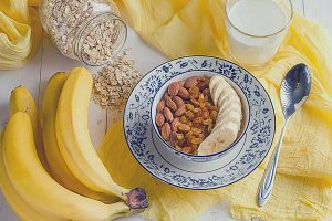 Oatmeal with banana, raisins, almonds and milk on a table