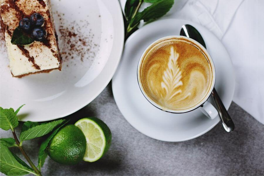 Cappuccino and cake on a plain white ceramic cup and plate - Bike more, eat more