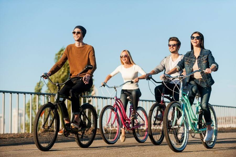 Four young people riding bicycles and smiling - Enjoying their social circle