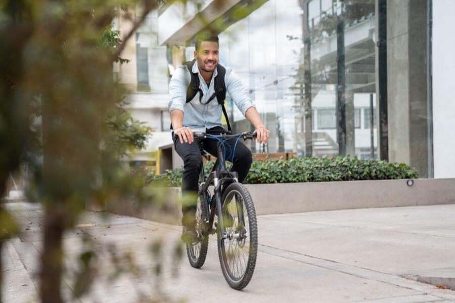 Happy man commuting to work riding a bicycle - Saves time on heavy traffic roads