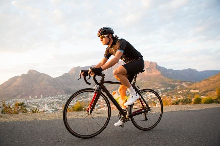 Male cyclist riding a bicycle alone on the road early morning - Doing a low impact sport