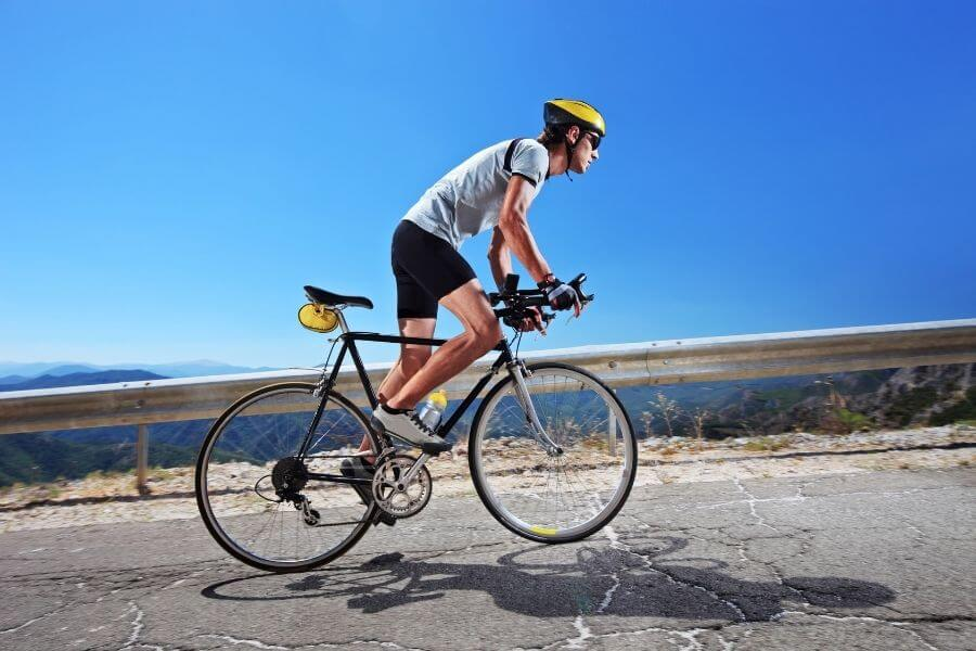 Male cyclist riding a bike uphill along road on clear summer day