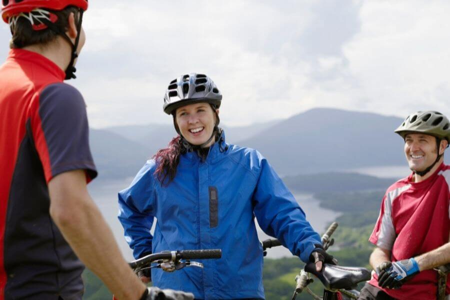 Three happy cyclists standing on top of mountain smiling
