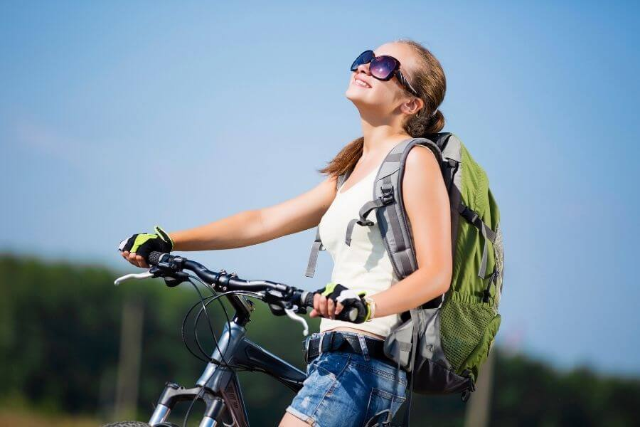Smiling young girl with backpack and bicycle along roadside on a sunny day  having positive mind